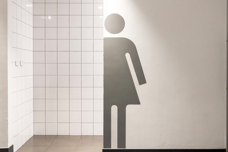 Restroom symbol a women on a toilet wall. Grey and white tone interior clean background.