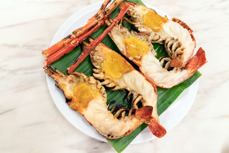 Charcoal grilled giant river prawn usually serve with spicy seafood sauce on green banana leaf in restaurant; Thailands popular dishes. Banco de Imagens