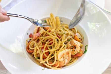 Mujer comiendo espaguetis con tenedor. Espaguetis de gambas al ajillo, aceite de oliva y ají. Foto de archivo