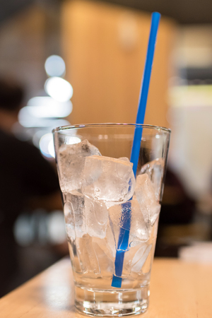 Glass of ice cubes with blue straw on wooden table at restaurant.