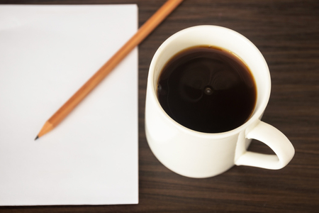 Black coffee cup with blank notepad and pencil on dark brown wooden table. Overhead shot