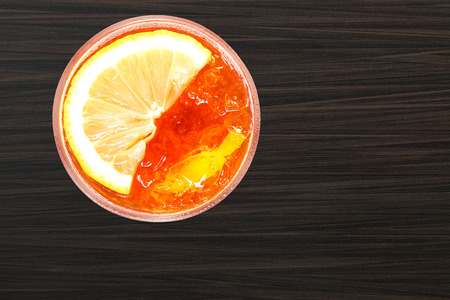 Ice black tea with lemon slice isolated on wooden table background, copy space. (overhead shot) Banco de Imagens