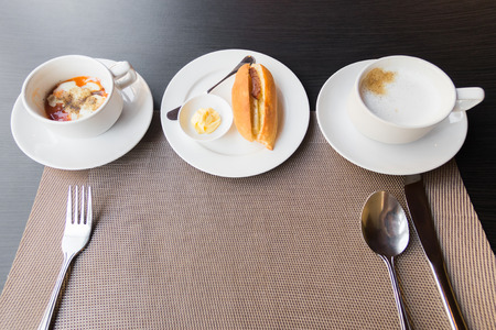 Breakfast meal on the table; soft-boiled egg, vietnamese baguette and coffee on table setting with table mat copy space.