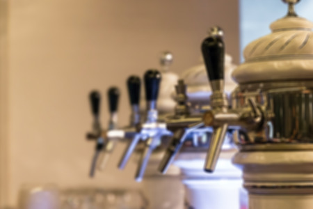 Blurred image for background of beer tap in row at restaurant or pub.