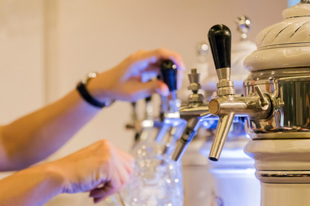 Beer tap in row with barman pouring fresh beer into the glass at restaurant or pub.