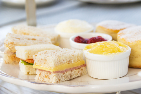 Sandwiches and butter scones on set English afternoon tea. Banco de Imagens