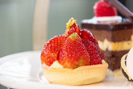 Juicy strawberry tart on pastry set English afternoon tea.
