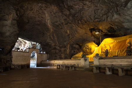 Reclining Buddha with light shinning through cave at Khao luang, Phetchaburi Province in Thailand.