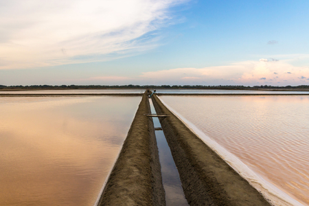 Salt farm with beautiful reflection of nature at sunset time in Na Klua - baan laem, Petchaburi,Thailand. Salt production is made from sea water and sunlight until dry into crystal.