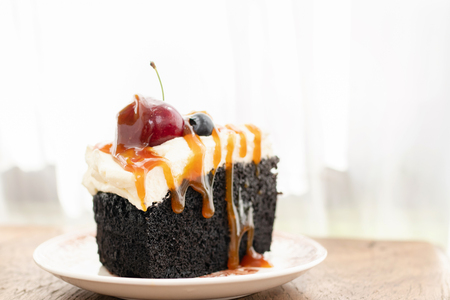 Dark beer chocolate cake (Chocolate Stout Cake) with caramel sauce and juicy fruits on top.