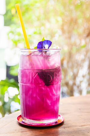 Butterfly pea with lemon juice on ice in transparent glass with summer garden background. Reklamní fotografie