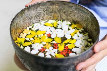 Flowers water in silver bowl. Preparing pour water on buddha statue and pour water on hands of senior for blessing on Songkran Festival in Thailand. Banco de Imagens