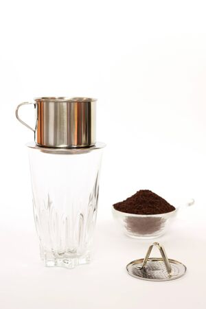 'Phin' traditional Vietnamese coffee maker, place on the top of glass, add ground coffee then pour hot water and wait until the coffee dripping into the glass with condensed milk at the bottom Banque d'images
