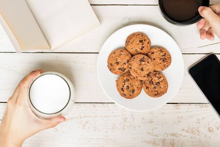 On the table : Two sides; balance your health and work concept. Milk and book or black coffee and phone with chocolate chip cookies on rustic wood table. Top view