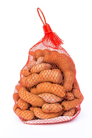 Sweet tamarind (Tamarind indica L.) in net package isolated on white background Foto de archivo