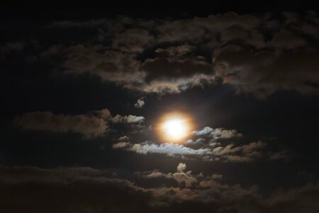 Full moon shining glowing light through the darkness of cloudy night sky; blur image for background.