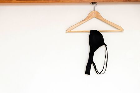 Black bra hanging on wood hanger on minimal open closet storage with copy space on wall background.