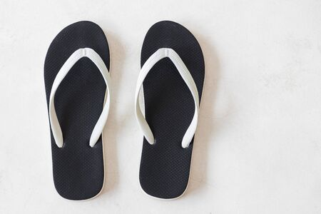 Black beach sandals on white floor with copy space. Overhead shot