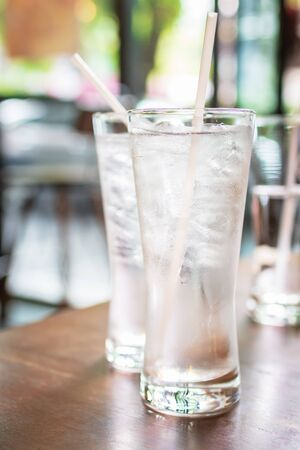 Glass of ice cubes with straw on wooden table at restaurant. Banco de Imagens - 128365273