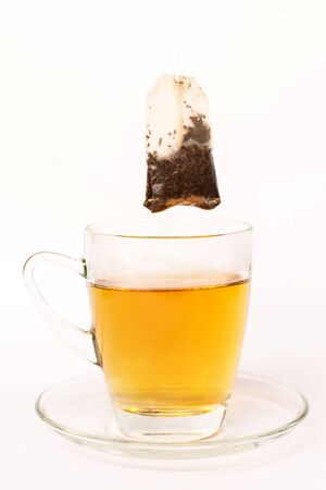 Tea bag dipped in the cup with hot water isolated on white background Stock Photo