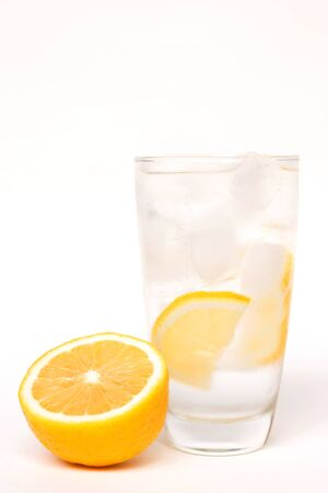 Glass of water on ice with lemon slice isolated on white background; popular morning healthy beverage Banco de Imagens - 128365443