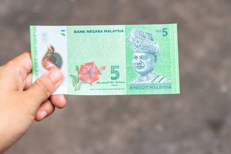 Five Ringgit Malaysia bank note on hand isolated on grey background.