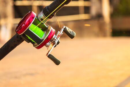 Closeup of fishing rod and reel with beautiful sunlight on background. 스톡 콘텐츠