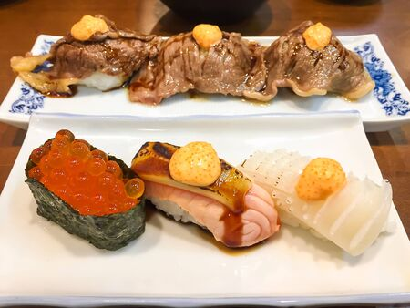 Different types of sushi on plate; Ikura, salmon, squid and wagyu beef sushi.