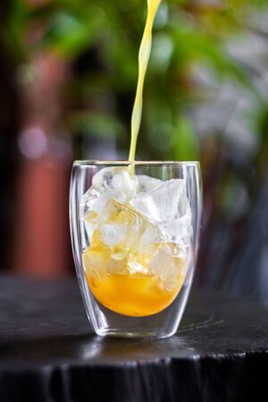 Pouring fresh orange juice on ice in glass on wooden table in a garden. Refresh your day.