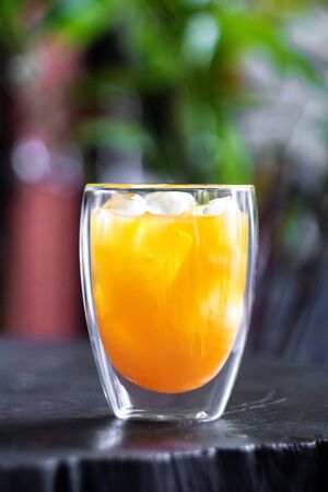 Fresh orange juice with ice in glass on wooden table in a garden. Refresh your day. 스톡 콘텐츠