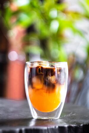 Iced fresh orange juice topped with espresso on wooden table in a garden, as sunrise coffee make a good day. 스톡 콘텐츠