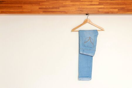 Light blue denim pants hanging on wood hanger on minimal open closet storage with copy space on wall background.