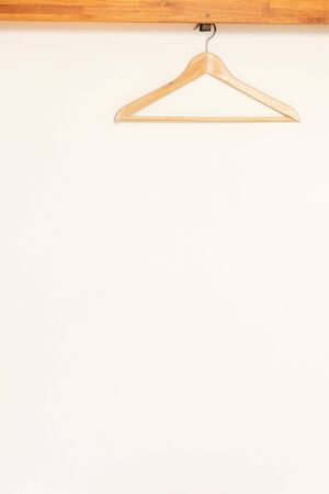 Wooden clothes hanger on rail in wooden open wardrobe