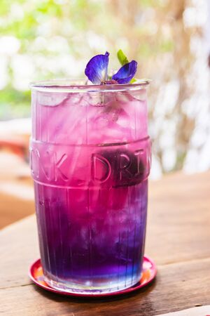 Butterfly pea with lemon juice on ice in take away glass with blur restaurant background.