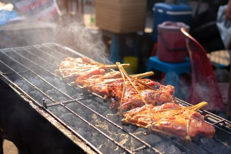 Grilled chicken marinated with curcuma on the charcoal stove, Thai street food market.