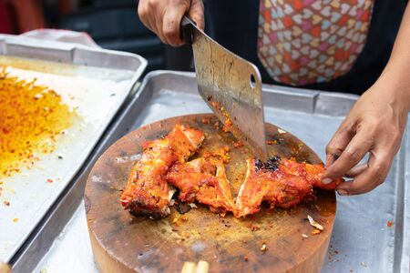 Street vendor cutting a grilled chicken marinated with curcuma on wooden cutting board, Thai street food market. 스톡 콘텐츠
