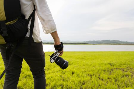 Young lady with backpack holding camera in beautiful nature background. Travel lifestyle vacations concept