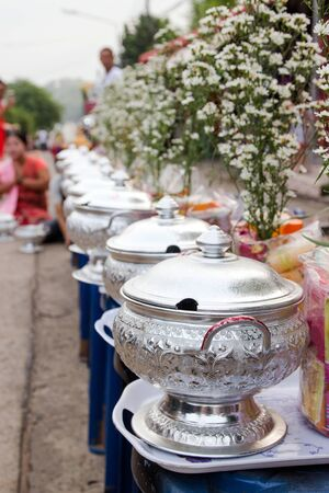 Line up rice in silver bowls sets of alms prepared for buddhist monk in morning at Sangkhlaburi Mon Village, Kanchanaburi, Thailand.