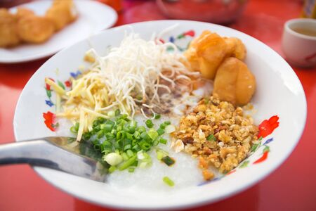 Pork rice porridge with soft-boiled egg, deep-fried dough stick, sliced ginger, spring onion and fried garlic served with hot chinese tea at local morning market. 스톡 콘텐츠