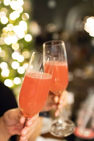 Cheers, clinking glass having a good time celebrating at party night with bokeh background. 스톡 콘텐츠