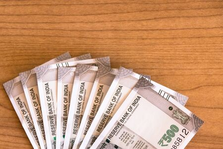 New series Indian five hundred rupee notes on wooden table background with copy space.