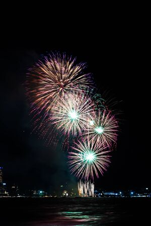 Fireworks over sea with city night on background. Festive colorful fireworks celebration in night sky.