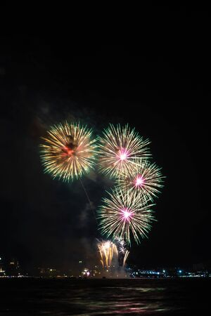 Fireworks over sea with city night on background. Festive colorful fireworks celebration in night sky. 스톡 콘텐츠