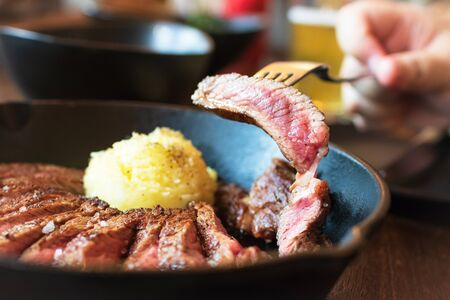 Cast iron plate with sliced grilled ribeye cooking a medium-rare steak with mashed potato and sauce in saucer over table.