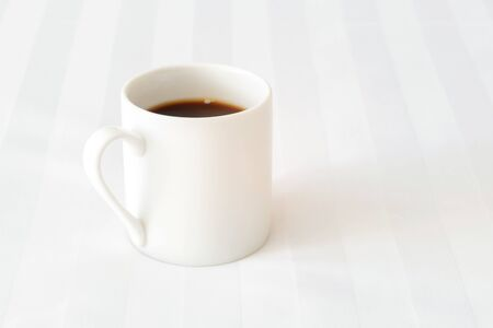 Black coffee cup on the bed in cozy morning with sunshine into window. 스톡 콘텐츠