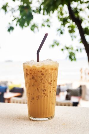 Iced coffee in a glass with the sea in beach bar on background.