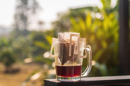 Tropfbrauen; klares Glas Kaffeetasse und Papiertropfbeutel mit gemahlenem Kaffee im warmen Sonnenlicht am Gartenbaum im Hintergrund.