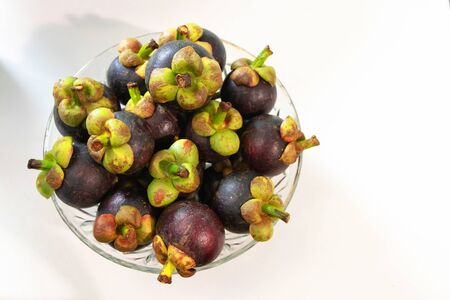 The purple mangosteen (Garcinia mangostana), known as the queen of fruits. Health benefits of mangosteen include a reduced risk of cancer, inflammation, allergies and diabetes.