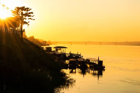 Silhouette boats in the river with beautiful sunset at Mekong river, Nong Khai in Thailand and the first Thai–Lao friendship bridge on background.