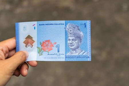 One Ringgit Malaysia bank note on hand isolated on grey background. Stock fotó